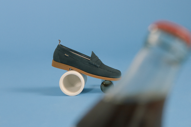 A black loafer sat in front of a blue backdrop.